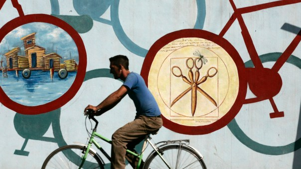 A man rides his bicycle past a wall painting in Cienfuegos, Cuba